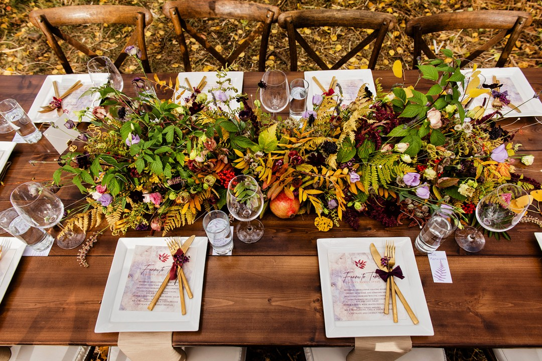 Tablescape featuring fall aspen leaves, beautiful flowers and farm to table menus