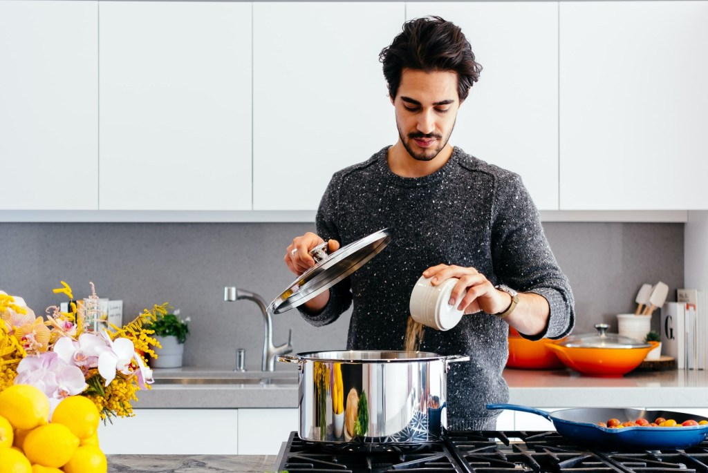 A person is dropping food into a pot of water in the kitchen.
