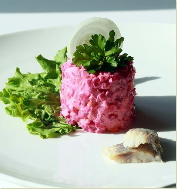 Shuba salad topped with fresh greens and onion with lettuce and fish on the side on a white plate.