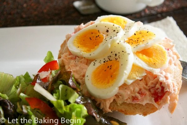 Salmon sandwich topped with boiled eggs and pepper with fresh salad on a plate.