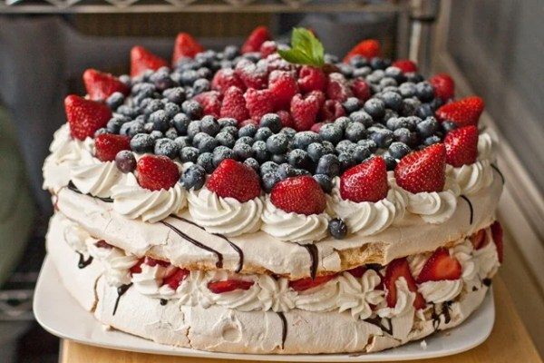 12 inch round gluten free cake recipe topped with whipped cream and berries between each layer.