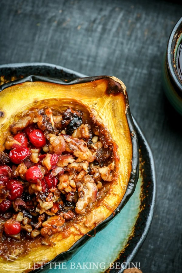 Close up picture of acorn squash stuffed with cranberries and walnuts on a plate.