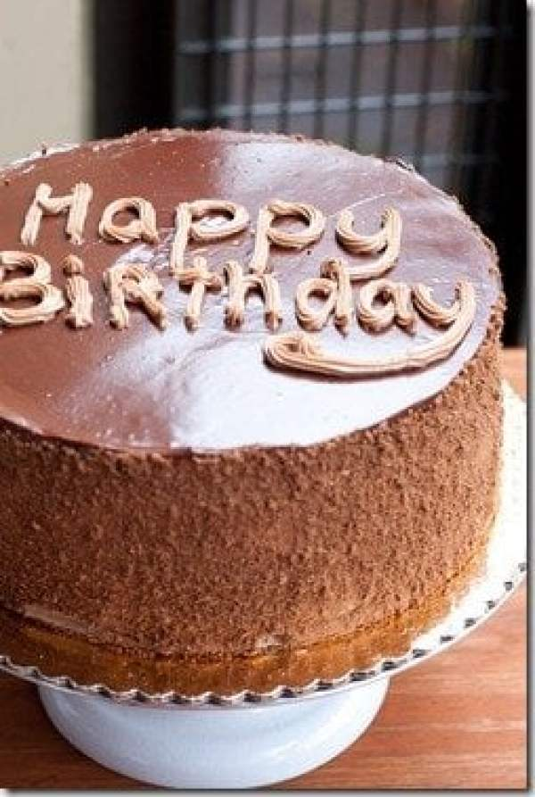 """Prague cake with """"happy birthday"""" written on top with frosting on a baking platter."""