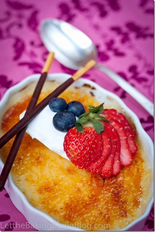 Close up picture of creme brulee in a white decorative bowl topped with strawberries and blueberries with two chocolate sticks with a spoon.