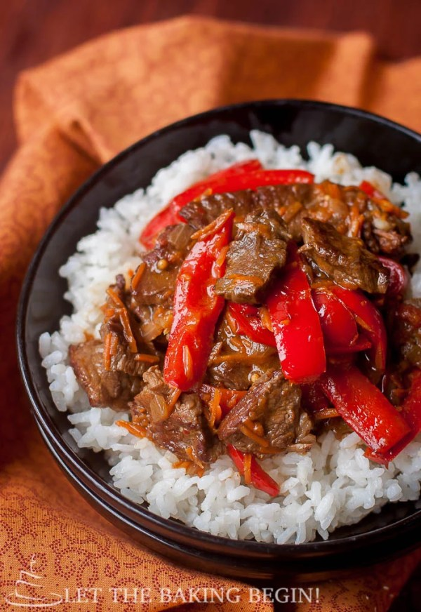 A bowl of white rice and spicy beef and bell peppers.