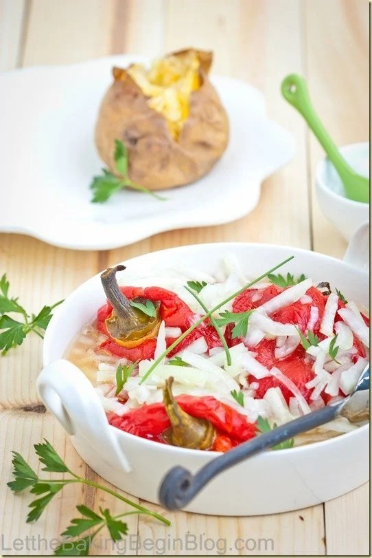 Roasted bell peppers in marinade topped with fresh greens in a white bowl.