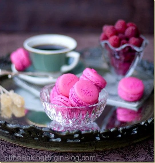 Raspberry Macarons in a glass bowl in a tray with raspberries and coffee.