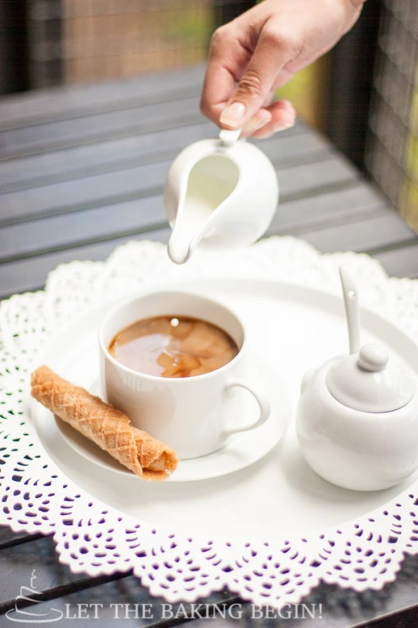 Crispy wafer on a white decorative plate with a cup of coffee on a white decorative tray.