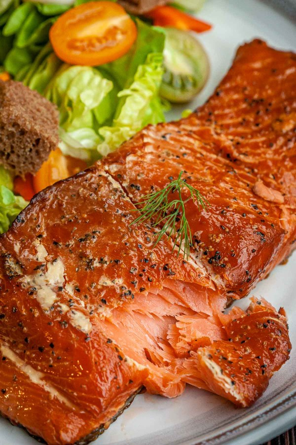 Smoked salmon fillet on a plate with seasonings, next to a mixed salad.