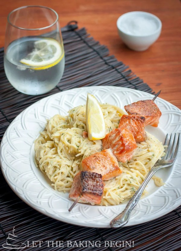 Oven grilled salmon kabobs sided with spaghetti noodles and a fresh lemon in a white decorative bowl.