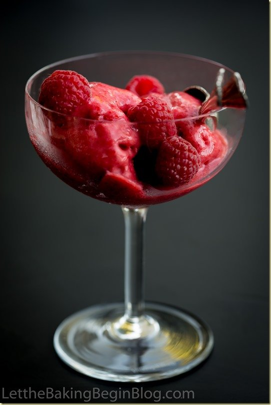 A cup of strawberry cream sorbet with fresh raspberries and a spoon.