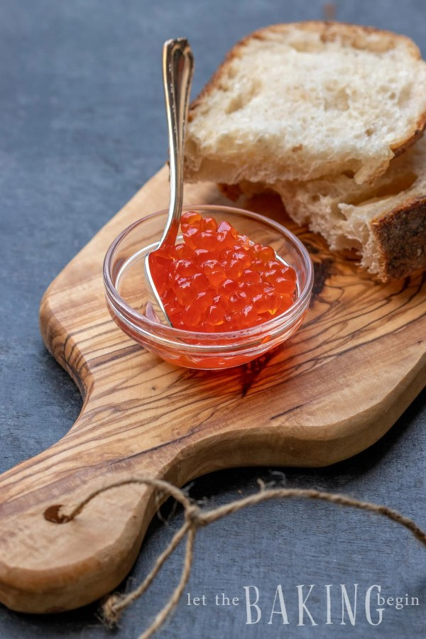 How to make Salmon Roe to Caviar - learn about the steps involved in getting the fish eggs to go from roe to caviar. The process is easy and simple. Wooden board with slices of bread and glass bowl with Salmon Caviar.