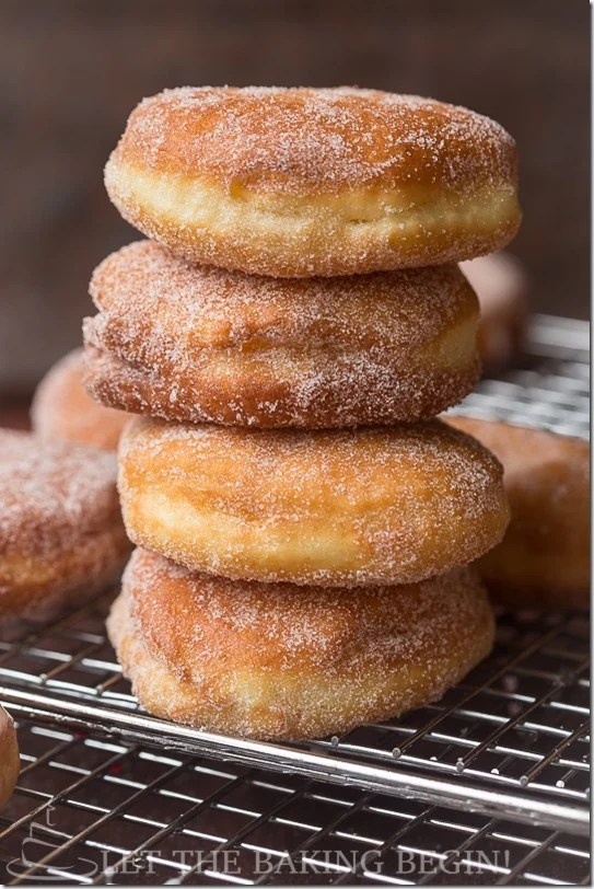Simple sugar-coated doughnuts stacked on top of each other on a cooling rack.