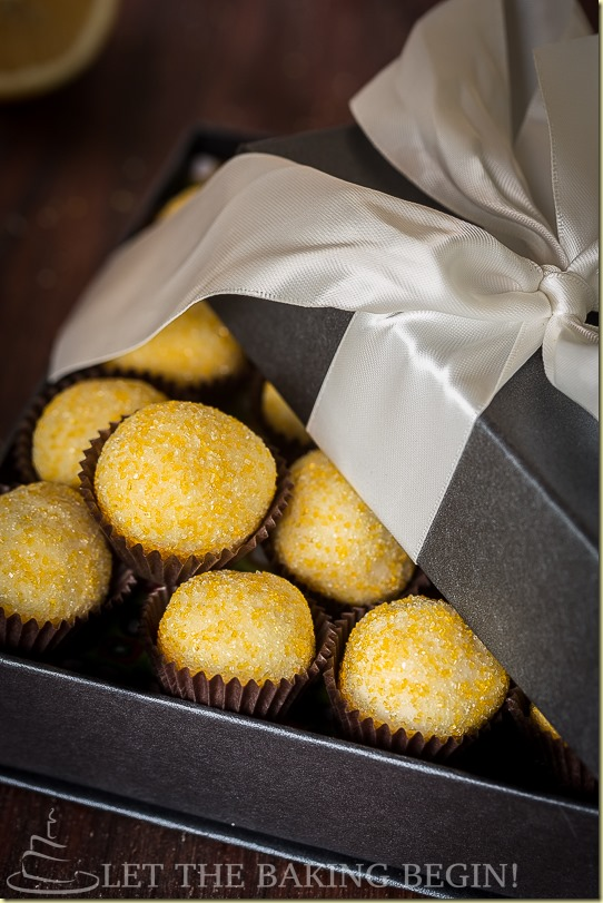 Lemon truffles in a decorative gray box with a big white bow.