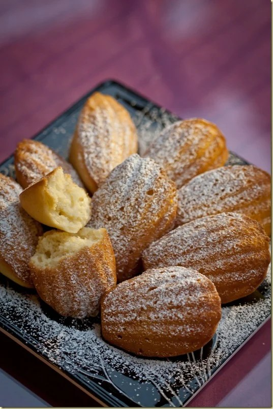 Lemon madeleines with one  broken in half on a black decorative plate topped with powdered sugar.