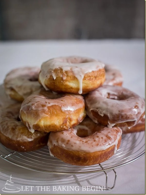 Super Soft Doughnuts with Sugar Glaze on a cooling rack stacked on top of each other.