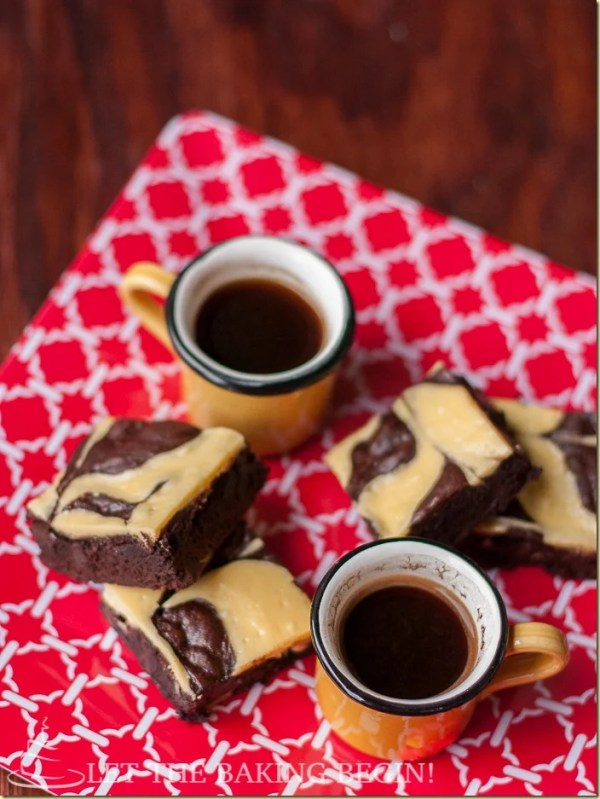 Lazy cheesecake swirl brownies on a tray with cups of coffee.