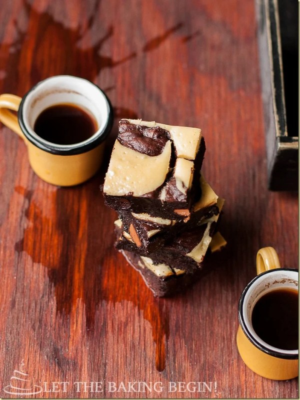 Lazy cheesecake swirl brownies with spilled coffee and two coffee mugs.