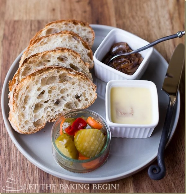 The best chicken liver mousse recipe served next to balsamic onions, vegetables, and bread all in a white plate.