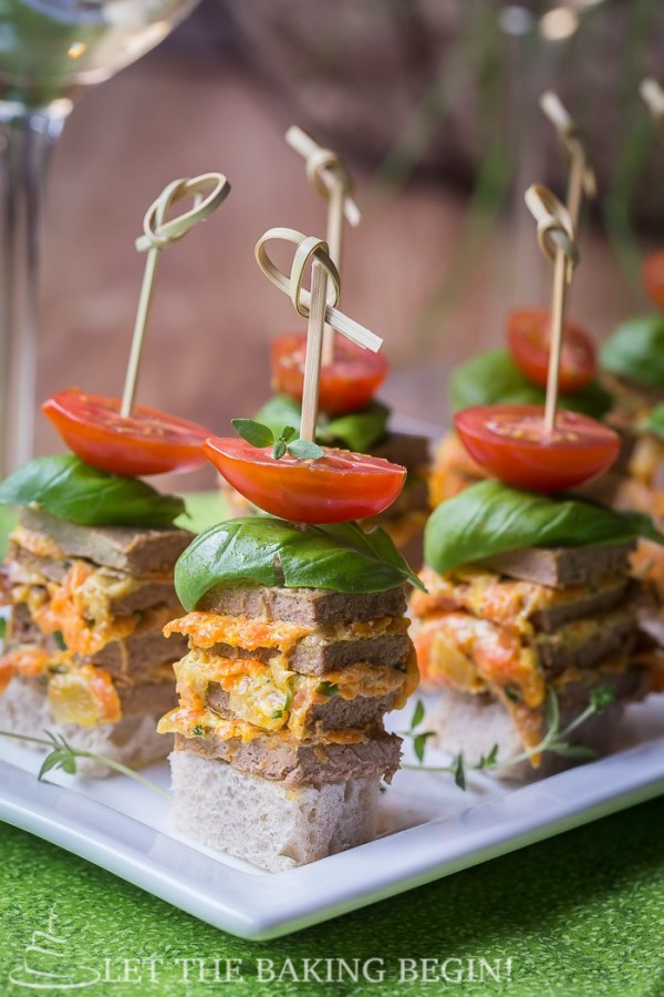 Chicken stacks with tomatoes on a white decorative plate.