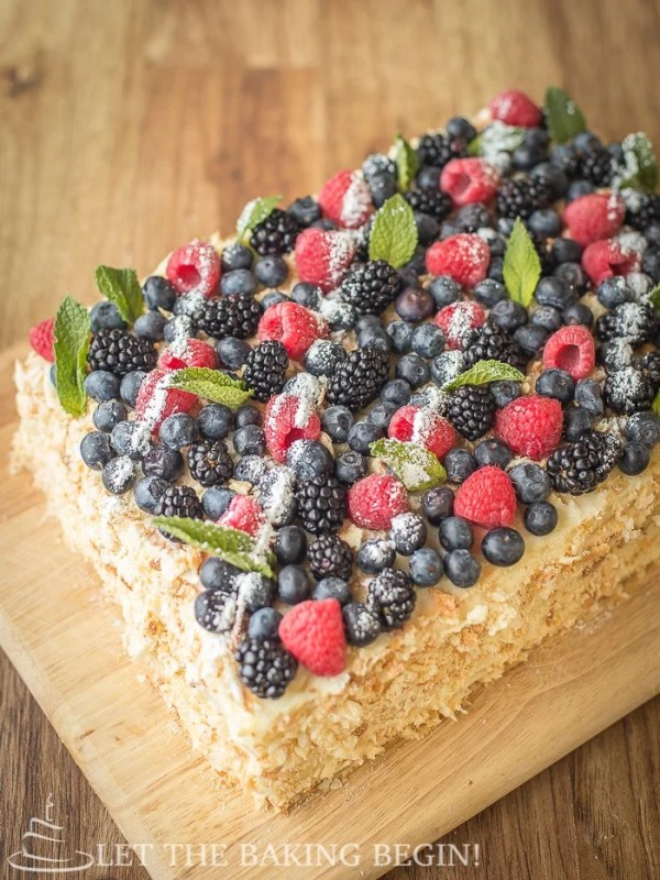 Full cake topped with raspberries, blueberries, blackberries, mint, and powdered sugar on a wooden cutting board.