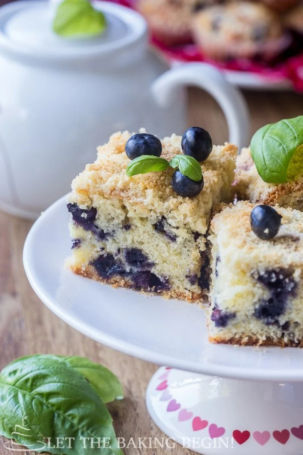 Blueberry cake topped with streusel toppings, blueberries, and mint on a white tray.