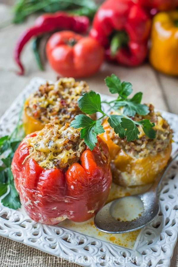Three stuffed peppers, two yellow peppers and one red peppers, topped with fresh greens in a white decorative plate.