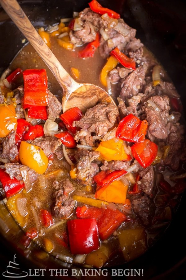 Spicy Slow Cooker Beef & Bell Pepper in a crock pot with sauce, and a wooden spoon. A simple recipe for beef recipes!