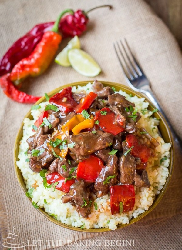 Spicy Cooker Spicy Beef & Bell Pepper in a bowl with rice. A fork on the side and peppers and limes.