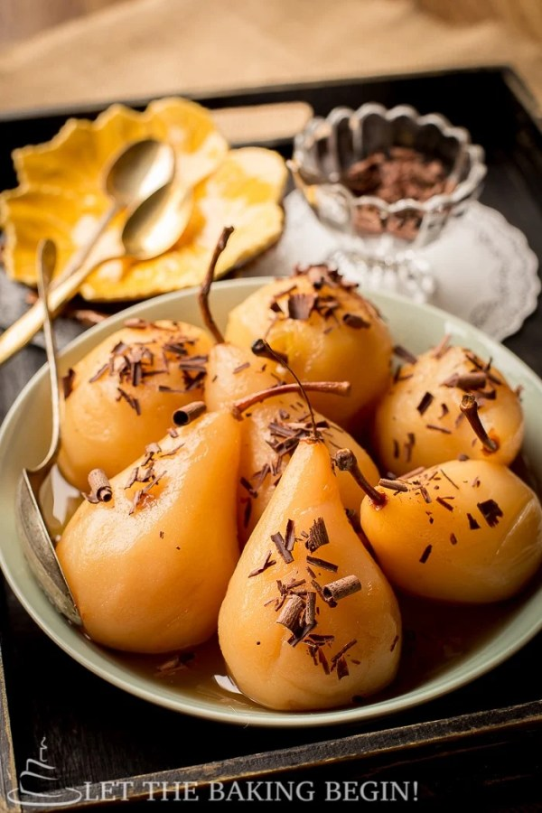 Poached pears topped with chocolate curls in a light green bowl in a wooden tray.