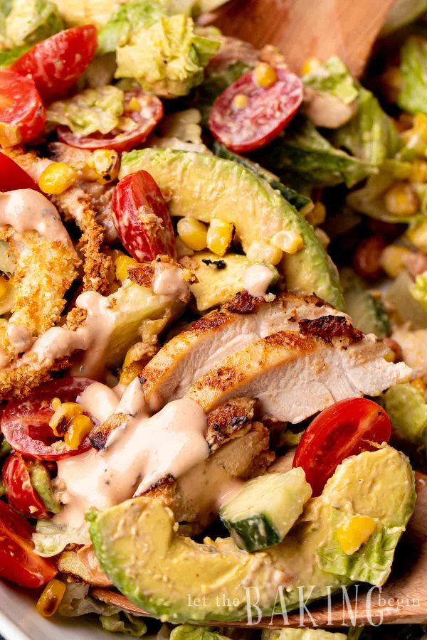Close up of a bbq chicken salad recipe tossed in homemade dressing.