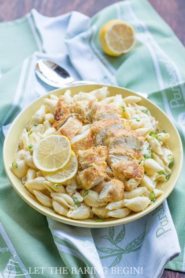 Cooked pasta topped with chicken tenders and fresh lemons in a yellow decorative bowl on a green napkin.