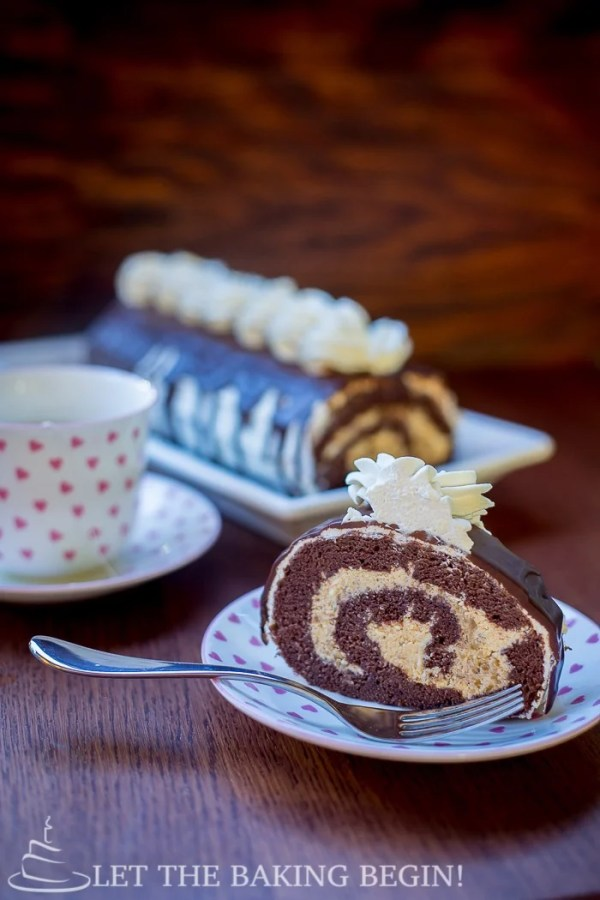 Slice of chocolate roll with walnuts topped with chocolate and chantilly cream on a decorative plate.