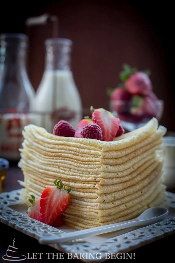 Choux pastry crepes folded and stacked on top of each other on a white plate topped with fresh berries.