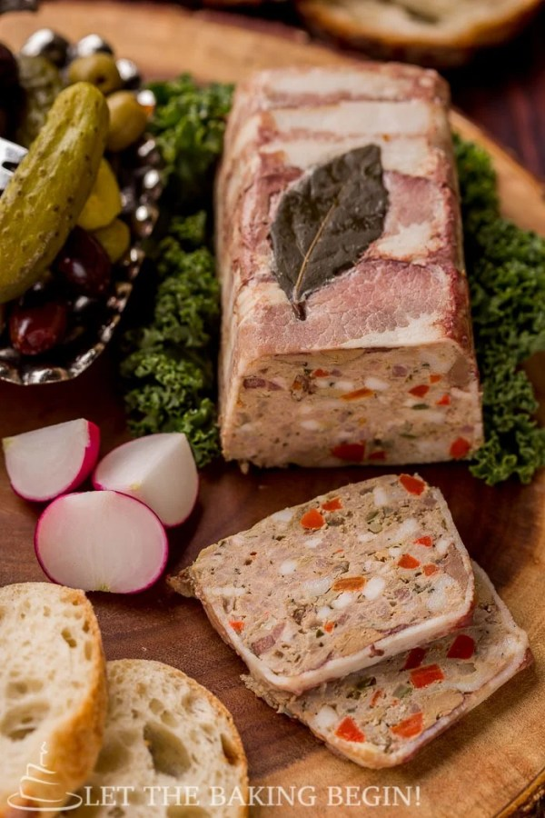 Country style pate on top of lettuce sided with radishes, slices of bread, olives and pickles on a wooden board.