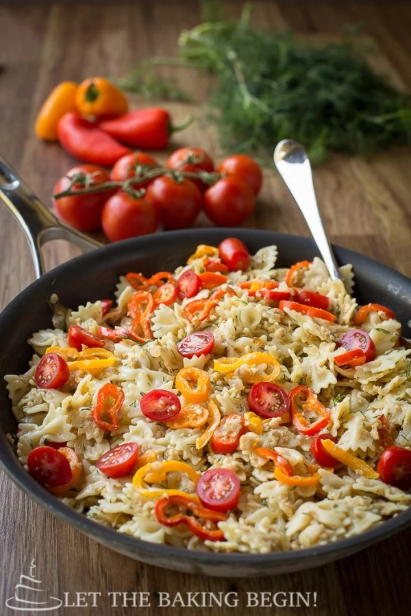 Turkey pasta recipe in a deep skillet topped with chopped tomatoes.