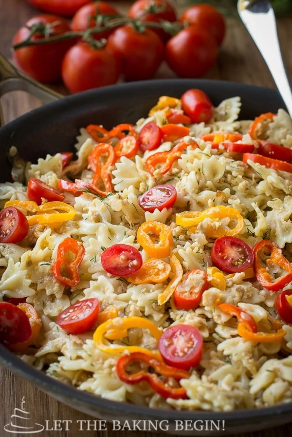 Leftover turkey pasta in a skillet with peppers and tomatoes topped with chopped fresh dill.