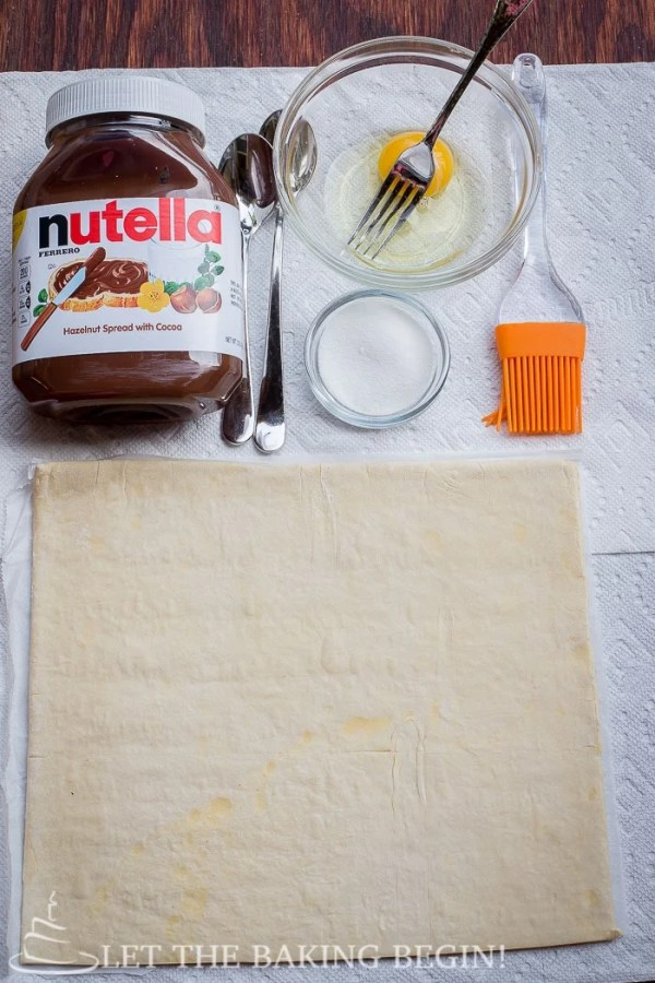 Nutella, egg wash and a puff pastry sheet on a paper towel.