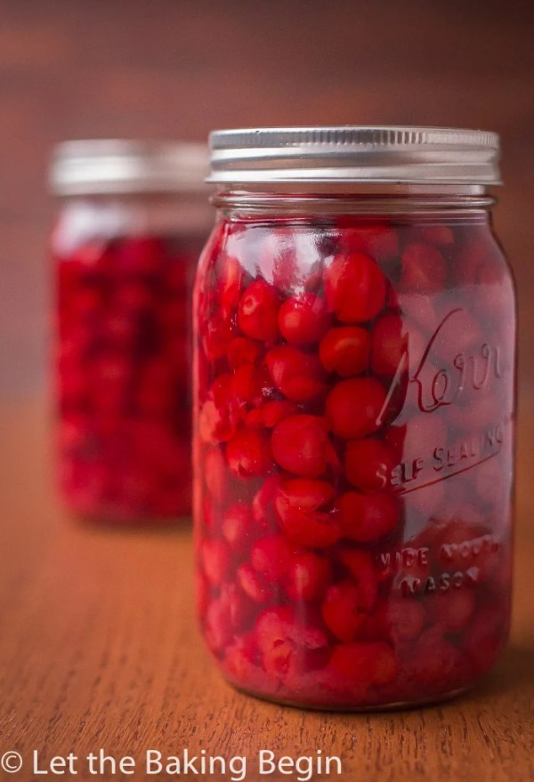 Close up picture of canned cherries in a mason jar on a counter top.