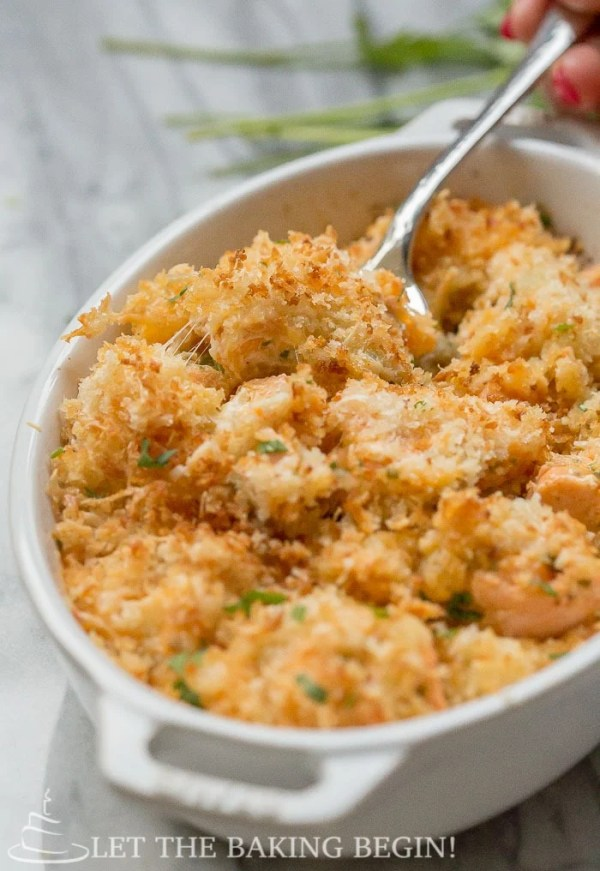 Up close picture of Cheesy Parmesan Crusted Salmon Bake in a casserole dish.
