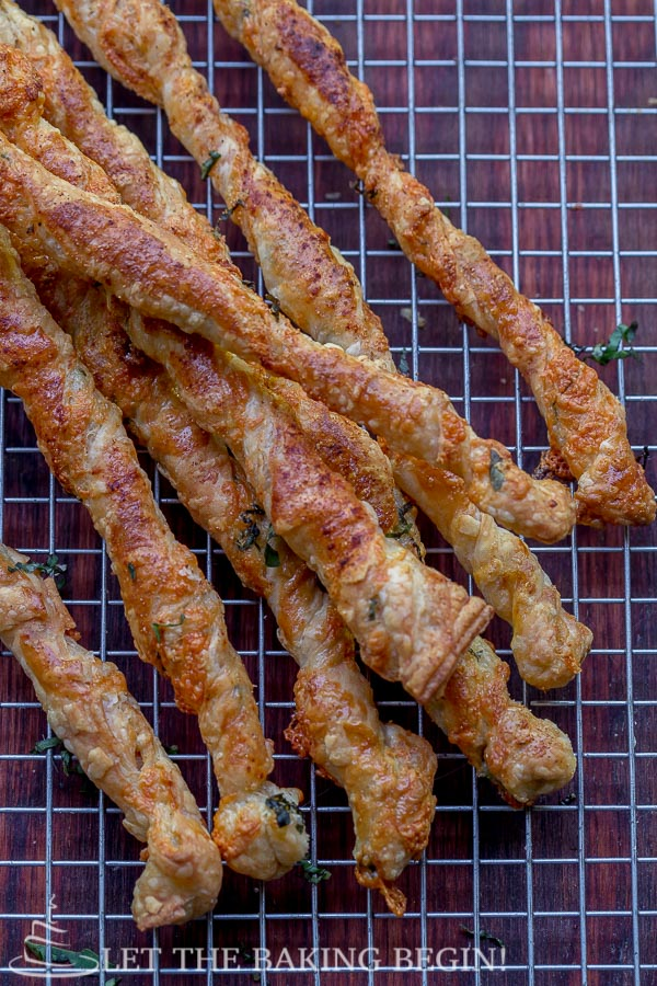 Close up of baked puff pastry twists on a cooling rack.