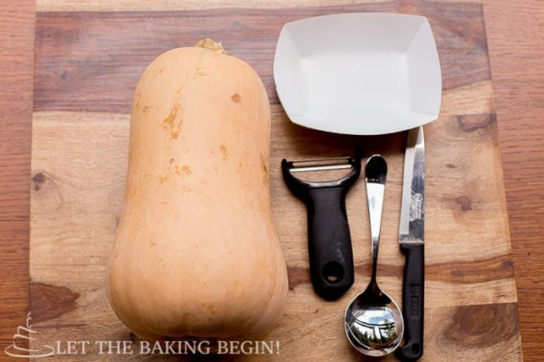 Butternut squash on a cutting board with a knife, spoon, and peeler.