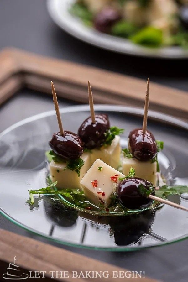 Marinated Darigold white cheddar cheese on toothpicks with olives.