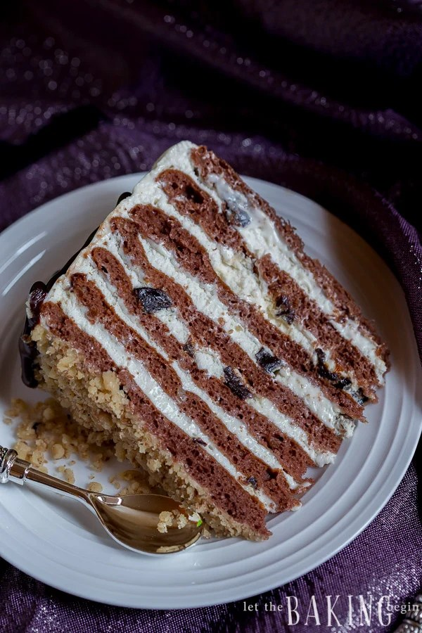 A slice of chocolate cake with layers of sour cream frosting and dried plums on a plate.