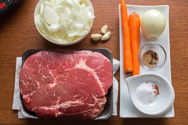 Beef chuck next to a carrot, onions, and seasonings.