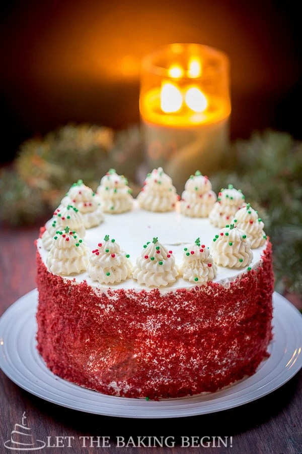 Red velvet cheesecake cake on a decorative plate topped with frosting and sprinkles.