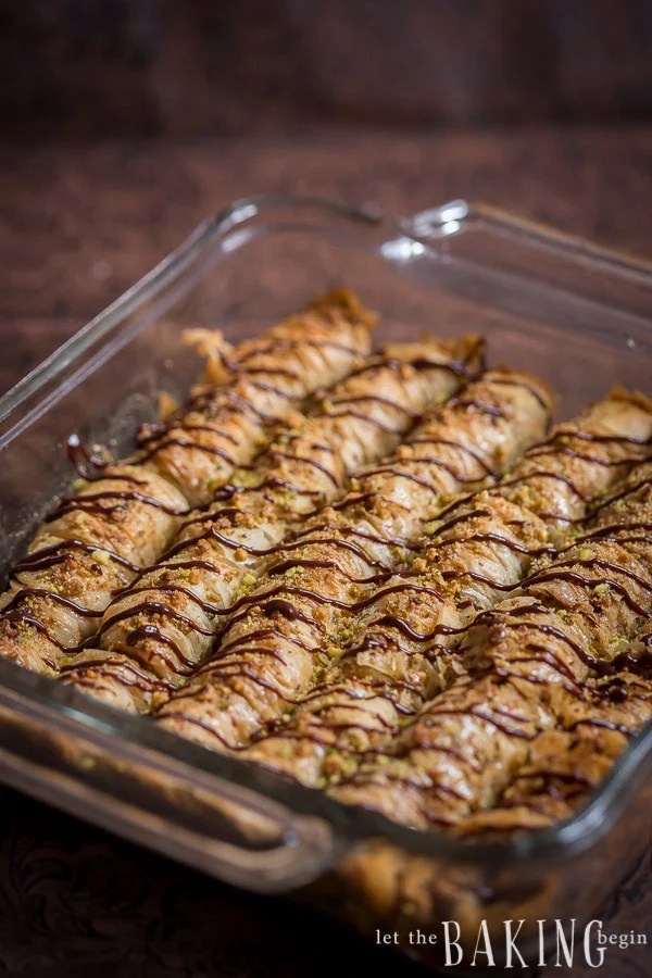 Baked baklava rolls topped with pistachios and chocolate in a baking pan.