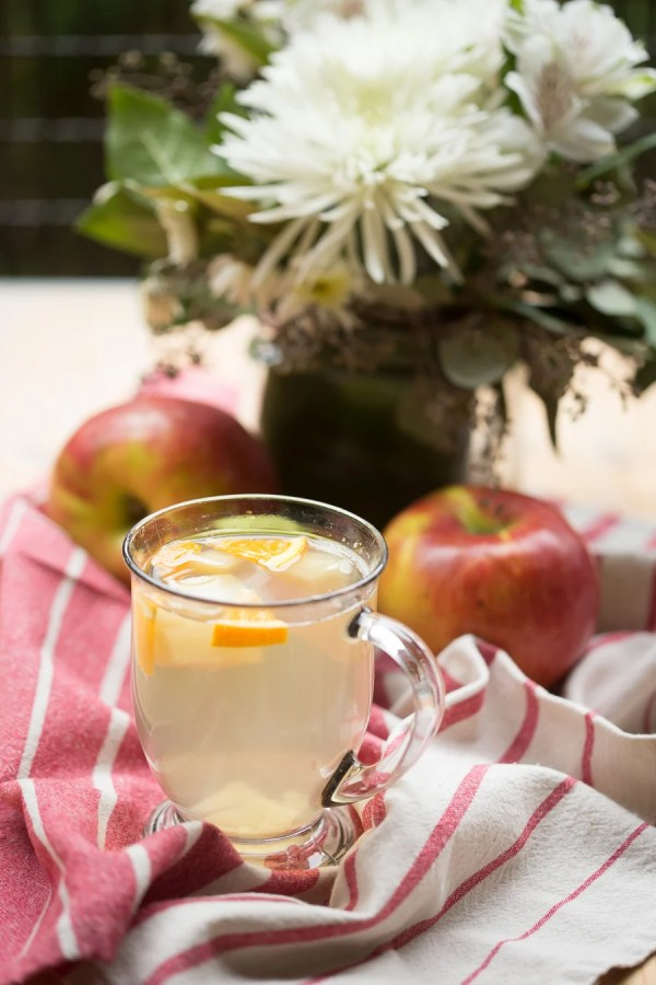Apple drink with orange slices on a red and white towel with apples and a vase of flowers.