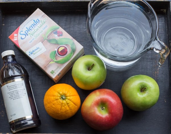 Picture of vanilla bottle, splenda, an orange, apples and water.