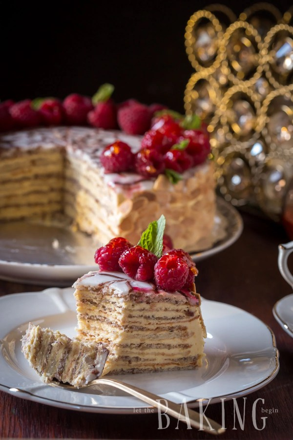 A slice of Esterhazy cake on a plate with a spoonful of cake.